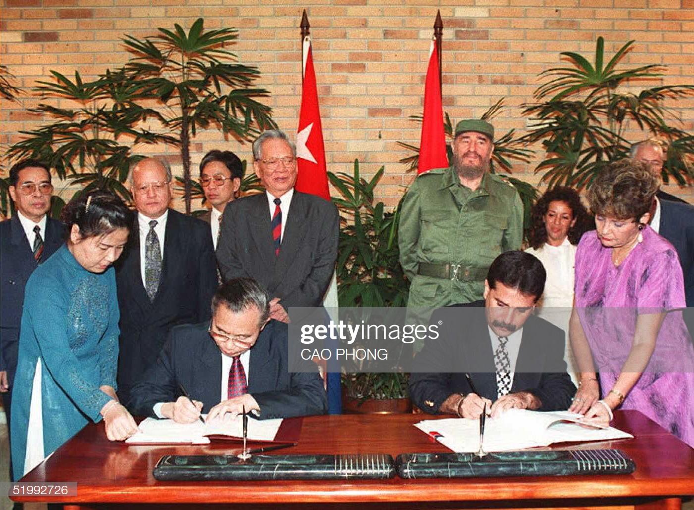 Bộ trưởng Ngoại giao Việt Nam Nguyễn Mạnh Cầm ký văn kiện hợp tác kinh tế với người đồng cấp Cuba, Chủ tịch nướcLê Đức Anhvà nhà lãnh đạo Cuba Fidel Castro đứng phía sau, Havana ngày 12/10/1995.